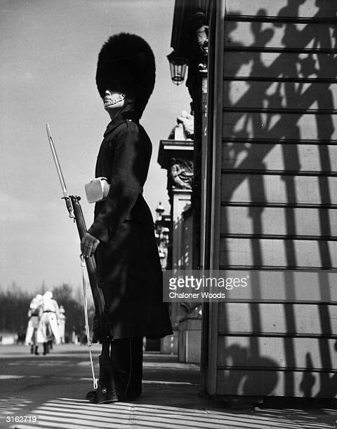 A uniformed guard stands outside the gates of Buckingham Palace in London with the distinctive busby shading his eyes