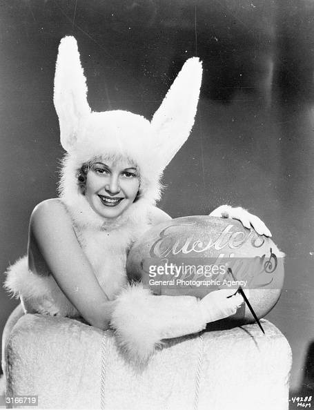 A woman wearing a rabbit outfit is writing 'Easter Greetings' on a large easter egg