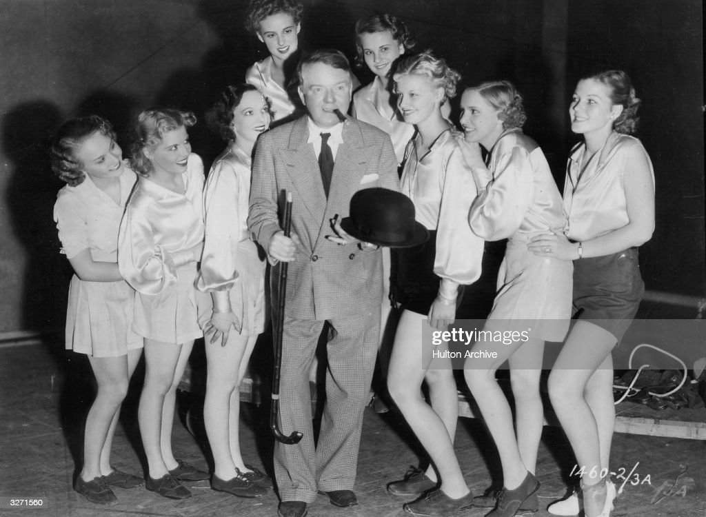 American comedian W C Fields with a walking stick a bowler hat a cigar and a large group of female extras during the filming of 'The Big Broadcast of...