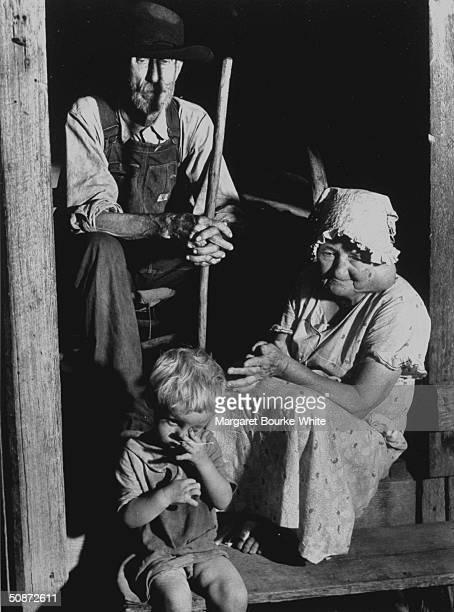 Elderly sharecropper his goiterafflicted wife sitting on the porch of their shack w their grandson
