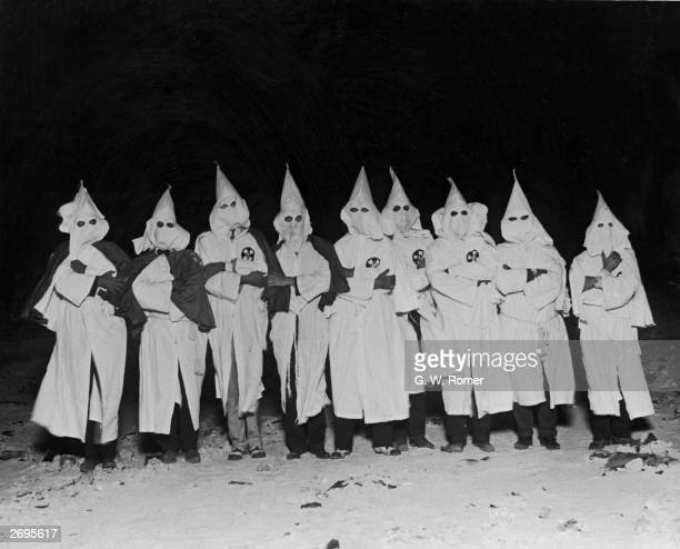 Fulllength portrait of Ku Klux Klan members standing in a row with their arms folded in white hoods and robes