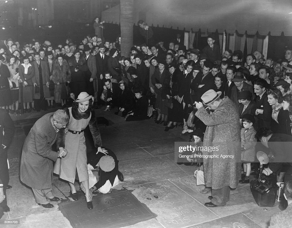Singing film star Deanna Durbin making a footprint in wet cement outside Grauman's Chinese Theatre Hollywood