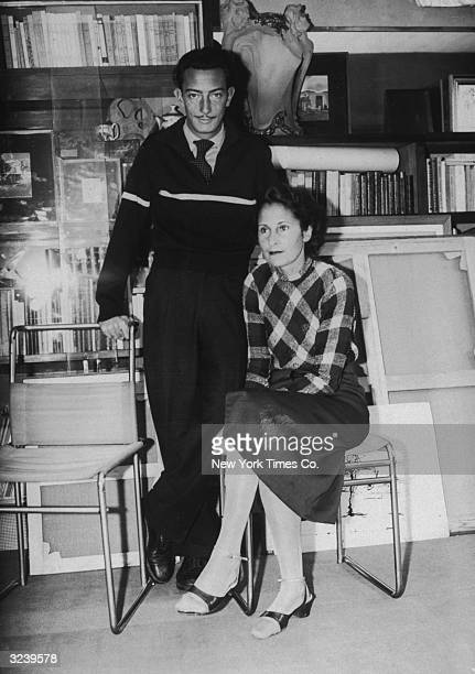 Spanish Surrealist painter Salvador Dali posing at home with his wife Gala shortly before leaving for New York where he would be exhibiting his work...