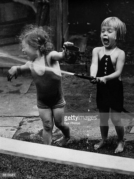 Two children seen here playing with a hosepipe in the garden of the Rhythmic Dancing School London