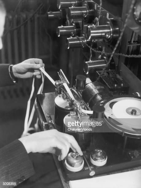 A close up showing a telegraph operator receiving a ticker tape message at a Cable Wireless office where telegrams are sent via Imperial