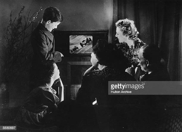 A family watch motor racing on their new television set