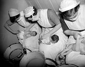 A group of nurses in face masks change a row of babies' nappies