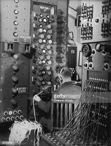 A telegraph operator receiving a ticker tape message at a Cable Wireless office where telegrams are sent via Imperial