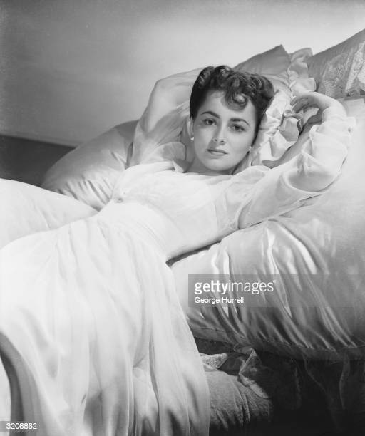 British actress Olivia de Havilland poses on a satin pillow in a flowing white gown See HF6803 for Hurrell setting up this photograph