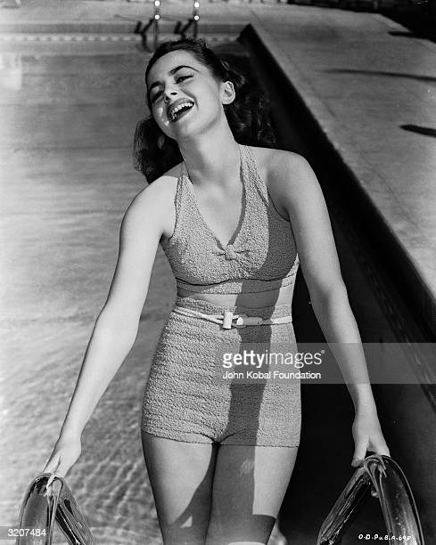 Britishborn actress Olivia de Havilland laughingly climbs the steps of a swimming pool
