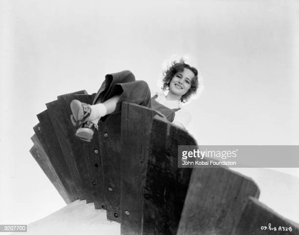Britishborn actress Olivia de Havilland swings her legs off the edge of a wooden spiral staircase