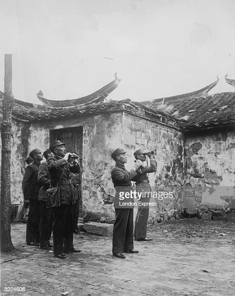 Chinese soldiers watching aeroplanes through binoculars during the SinoJapanese conflict