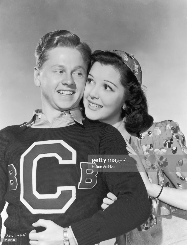 Promotional portrait of American actor Mickey Rooney and Canadian-born actor Ann Rutherford smiling cheek-to-cheek for director George B. Seitz's film, 'Out West With the Hardys'. Rooney is wearing a varsity sweater. Rutherford is wearing a floral print top with a matching cap.
