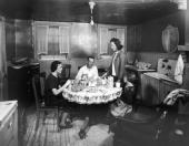 A family sits down to a meal in the kitchen of a basement flat at 63 Center Street later site of a housing project in the Red Hook neighborhood of...