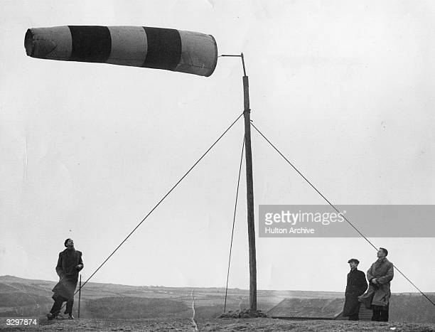 A fierce wind lifts the windsock at an airfield