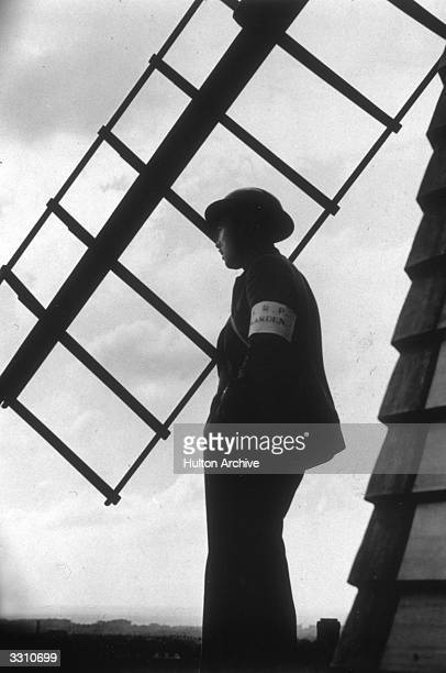 A silhouette study of an ARP warden standing beside a 200 yearold windmill which was used as an ARP post during World War II