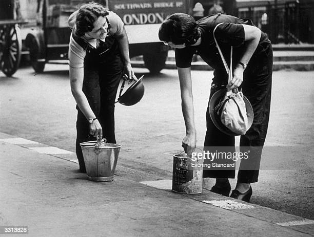 Ambulance workers paint the street kerbs white in order to assist them to drive at night from their London depot