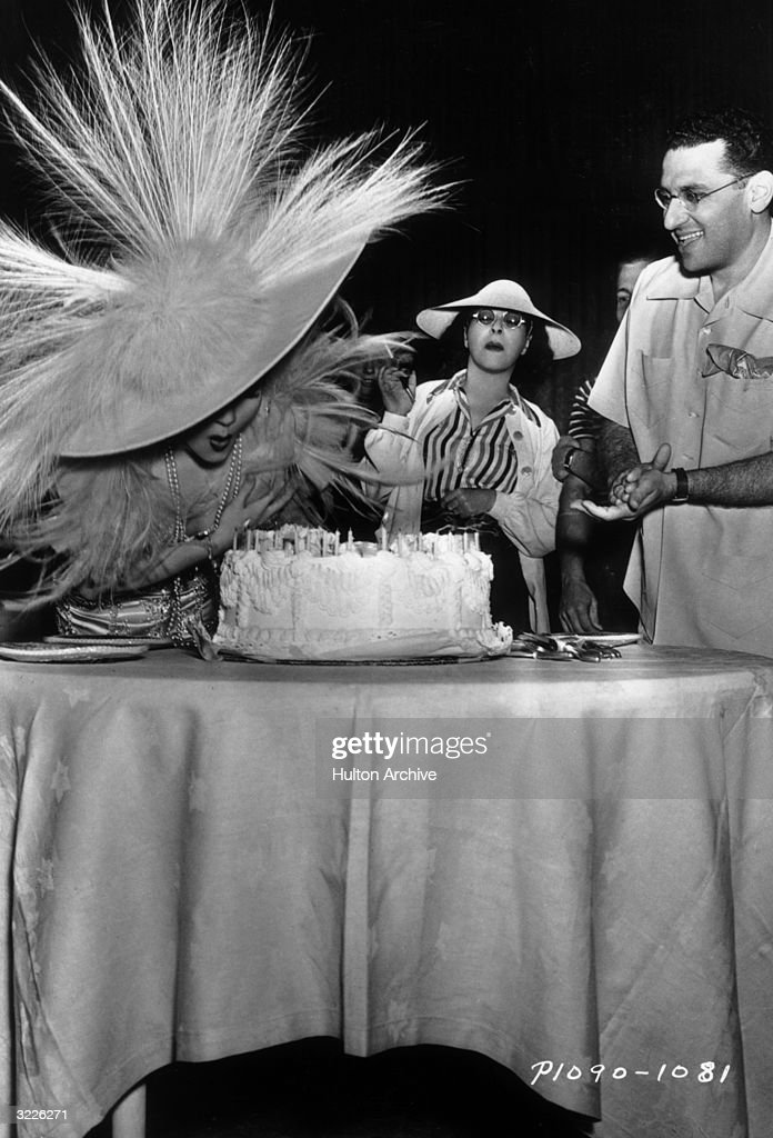 French-born actor Claudette Colbert (1903 - 1996) (left) blows out the candles on her birthday cake as American film director George Cukor, American costume designer Edith Head (center), and others look on, on the set of Cukor's film, 'Zaza'. Colbert, in costume as the title character, is wearing a hat and dress with long plumes.