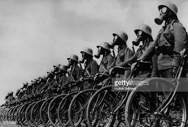 Fulllength view of members of the German light machinegun Cyclist Corps wearing gas masks while standing next to their bicycles in a lineup in...