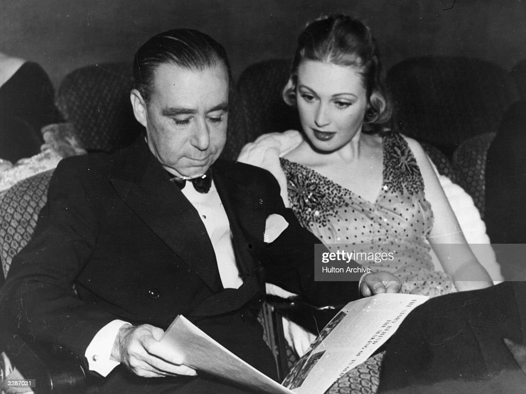 Hollywood film director A C Blumenthal reading a newspaper in the company of June Lang at a premiere.