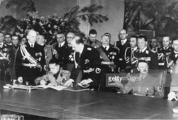 Italian politician Count Galeazzo Ciano Mussolini's soninlaw signing a document Also in the group are German dictator Adolf Hitler and behind him...