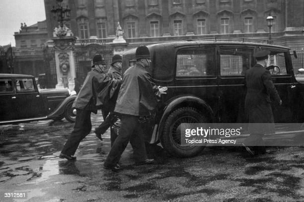 Policemen pushing away a car which broke down outside Buckingham Palace London