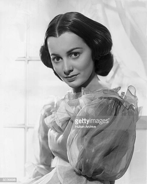 Promotional studio portrait of American actor Olivia de Havilland standing in front of a window in a promotional portrait for 'Gone With The Wind'...