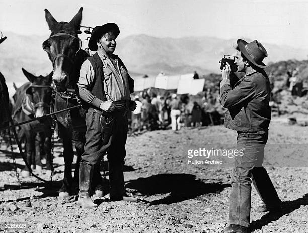 Wallace Beery and his nephew Noah Beery take turns snapping each other while on location in Death Valley for three weeks during the filming of '20...