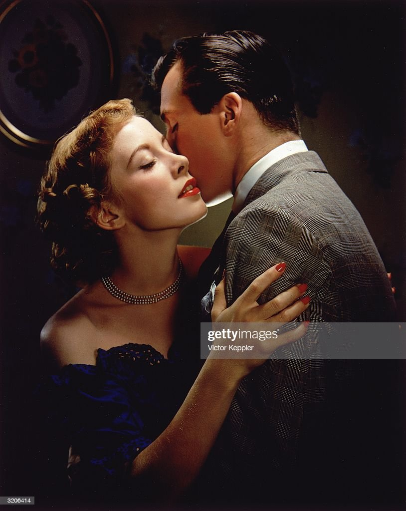 A couple embraces; the woman closes her eyes as her lover kisses her cheek. She wears a strapless dark blue dress and beaded necklace.