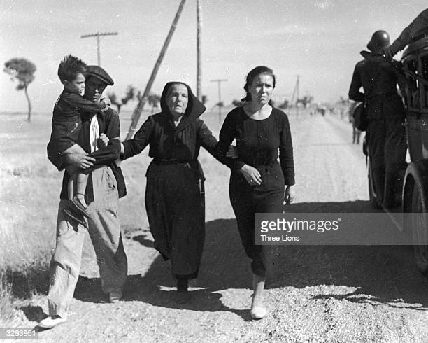 A family of Belgian refugees hold and support each other as they pass a military vehicle while walking the road to France Behind them are other...