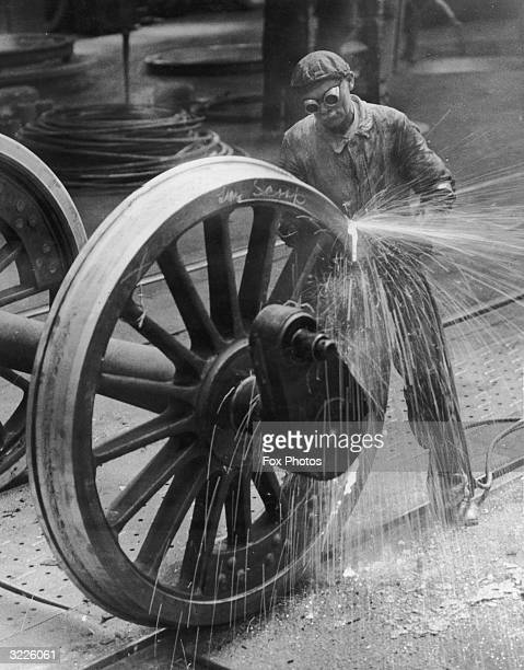 A man wearing goggles making sparks while working on a large steam engine wheel
