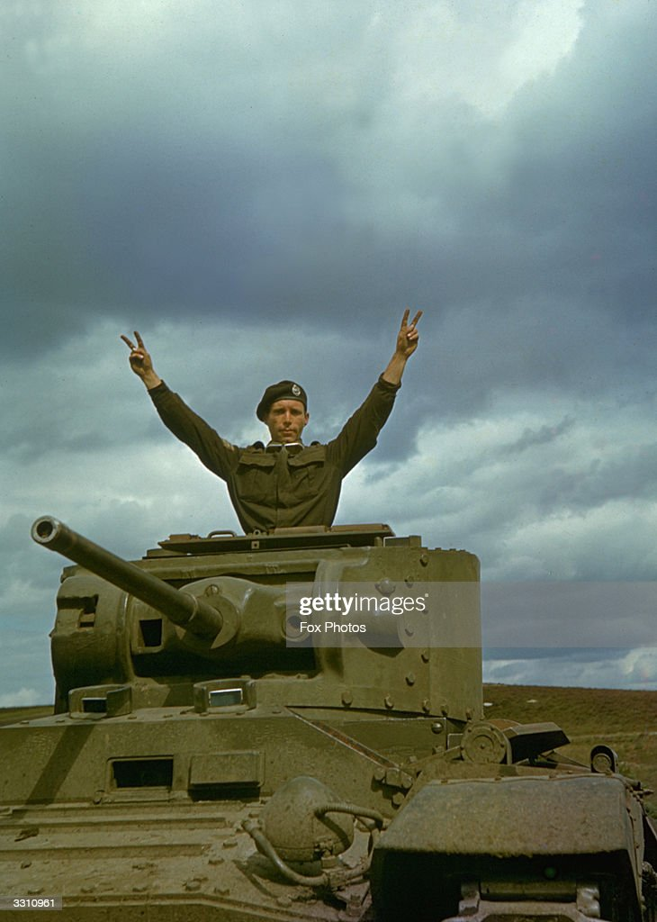 A member of a British tank regiment makes the victory sign from the top of his vehicle