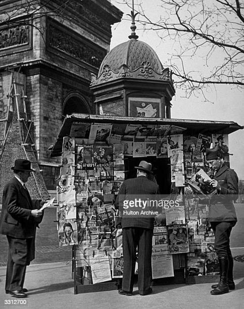 A soldier in Paris reading Picture Post at a newsstand