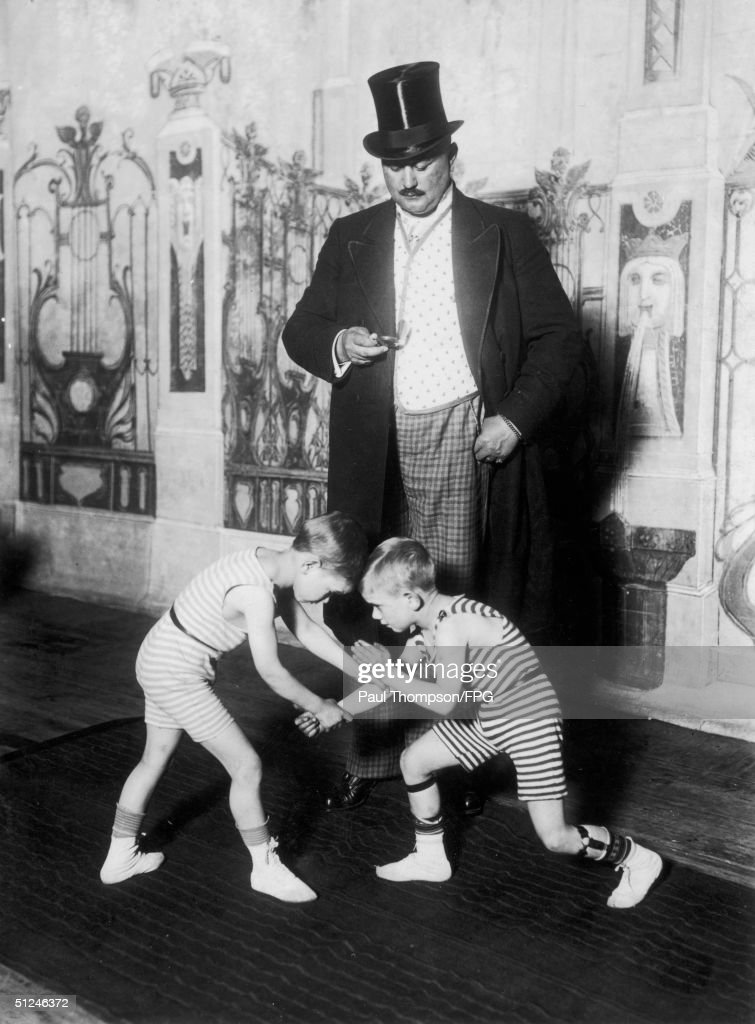 Circa 1940 A wrestling match in miniature two small boys confront each other at the Berlin Circus sideshow