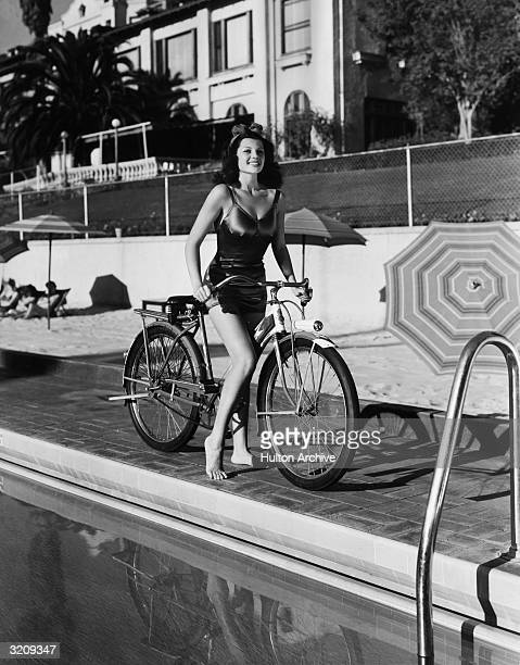 American actor Rita Hayworth poses on a bicycle in a swimsuit by the side of a swimming pool at the Beverly Hills Hotel California