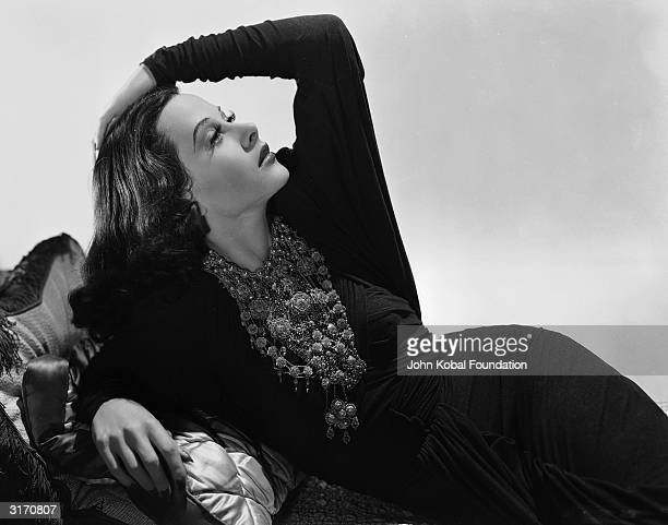 Austrian born actress Hedy Lamarr reclines on a cushion covered chaiselongue with hand on head