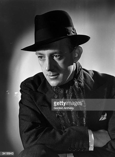 British actor Alec Guinness wearing a hat and cravat
