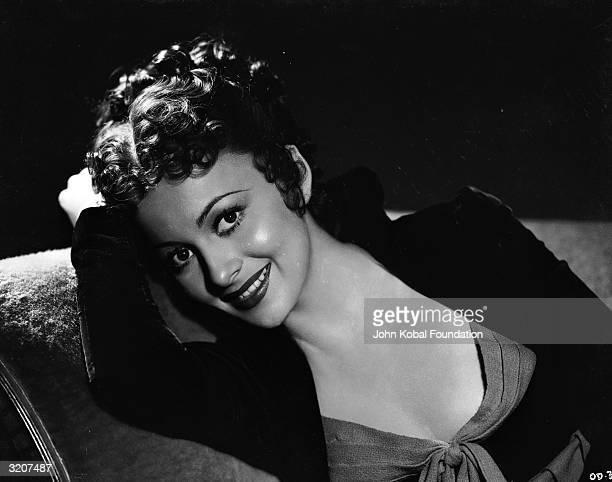 Britishborn actress Olivia de Havilland leans smiling against the arm of a sofa