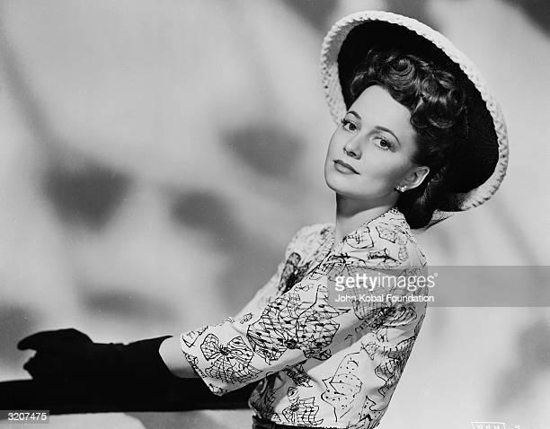 Britishborn actress Olivia de Havilland wearing a widebrimmed hat and printed dress