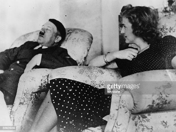 German dictator Adolf Hitler asleep in an armchair watched by his mistress Eva Braun