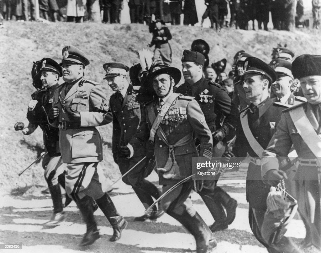 Italian fascist dictator Benito Mussolini (1883 - 1945) leads his officers in a spirited run in full military regalia.