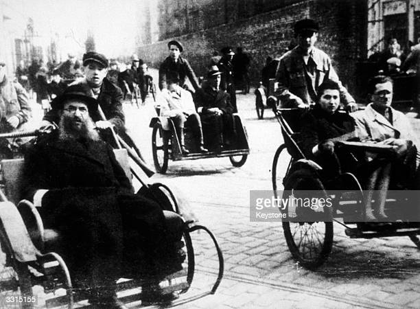 Jews in rolling chairs in the walled ghetto of Warsaw Subsequently almost all the population of the ghetto were slaughtered by the Nazis