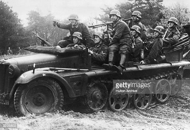 Nine German soldiers ride in an armored allterrain troop carrier armed with machine gun turrets World War II The vehicle uses large front tires and...