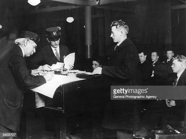 Officials interviewing immigrants at Ellis Island New York and making a record of every one