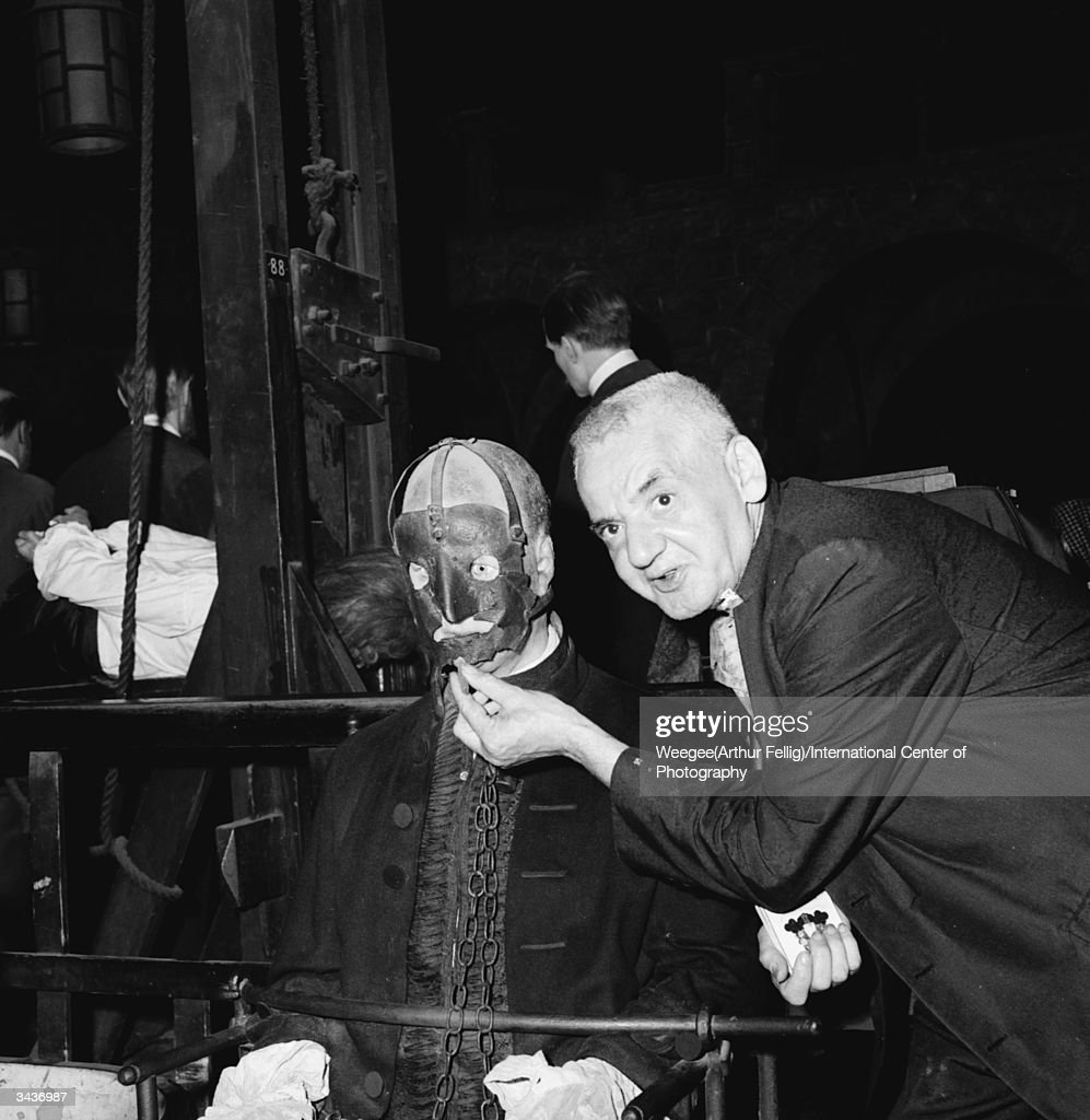 Polish-born American photographer Arthur 'Weegee' Fellig (1899 - 1969) inspects a model of a condemned man before the guillotine, at a grisly waxwork museum. (Photo by Weegee(Arthur Fellig)/International Center of Photography/Getty Images)
