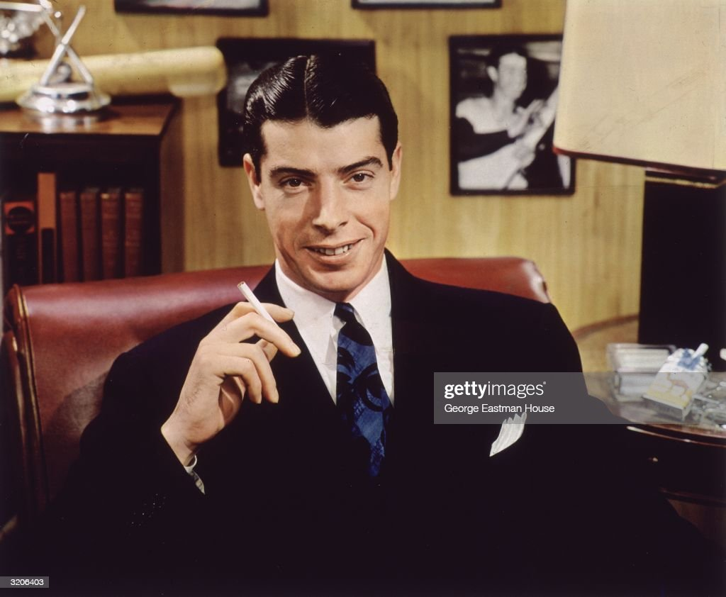 Portrait of American baseball player Joe Dimaggio (1914 - 1999) wearing a dark suit and holding a cigarette in a promotion for Camel Cigarettes.