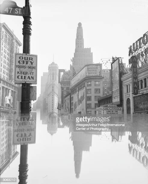 The junction of Times Square and Herald Square on 47th Street New York City A mirror image makes the scene appear as if half the street is flooded...