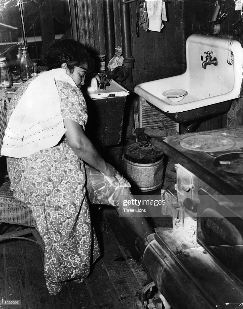 There is no running water in this shack where a family of war workers live in Newark New Jersey The woman has to carry water in a bucket and wash as...
