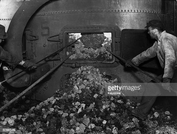 Two employees at the Astoria manufacturing plant of the Consolidated Edison Company of New York clean the furnace in preparation for the addition of...