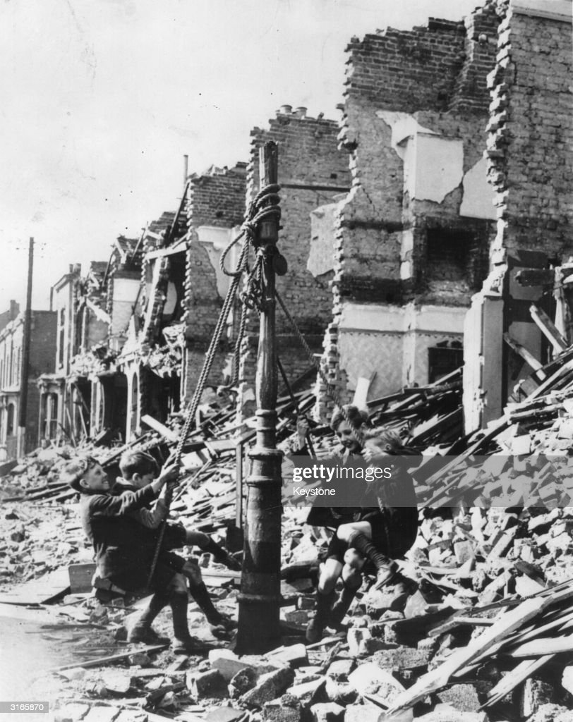 Young boys swinging from a lamp post in the midst of rubble left by a bombing raid on London during the Blitz.